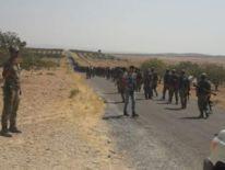 FSA fighters walking along a road towards Jerablus