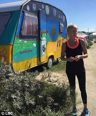 She stands outside Allam's brightly coloured caravan in the Jungle